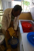 Abdi's employees pour the newly purchased milk into a container where it will be refrigerated until it is sold to customers. Thanks to refrigeration installed at central collection shops like Abdi's, women like Dhaki who aggregate and sell milk can avoid spoilage, make a larger profit, and have time to attend to other household duties.