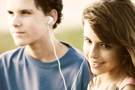 Teens sharing earphones, listening to music outdoors in the summer time.  Photo by  SCA Svenska Cellulosa Aktiebolaget