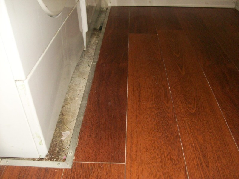 A Hardwood Floor Installation Guide for Both Engineered and Non     Aluminum 1X1 angle used as trim around a washing machine pan