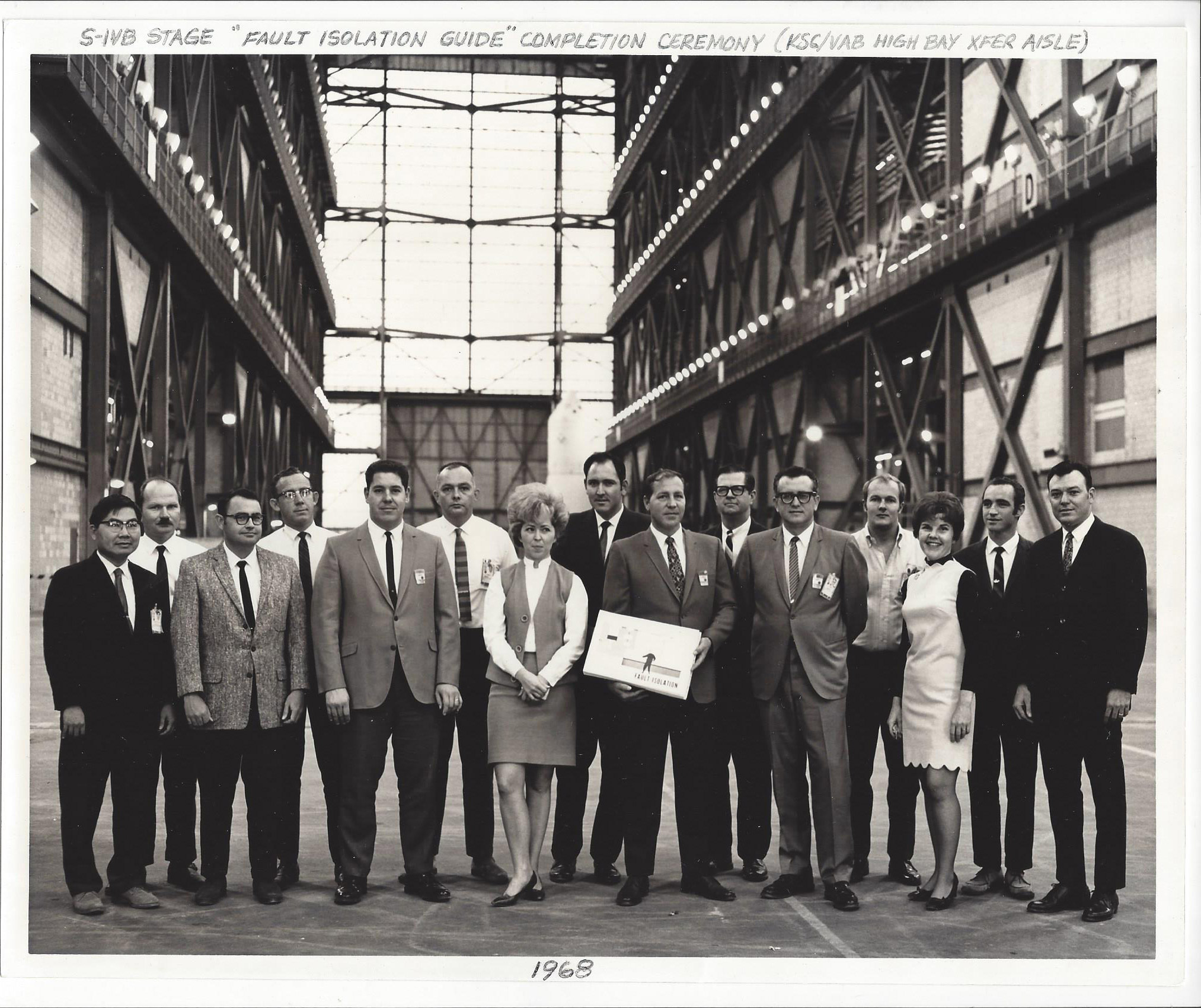 "Group photo of personnel who assisted in production of the ""Fault Isolation"" document that was written by five engineers in 1968. This document was to be used for automating troubleshooting on the various systems of the Saturn V third stage called S-IVB built by MDAC. Jim was one of the five engineers responsible for producing description and schematics for the J2 engine, telemetry, and measuring systems. Photo taken in the transfer aisle of the massive Vehicle Assembly Building at KSC."