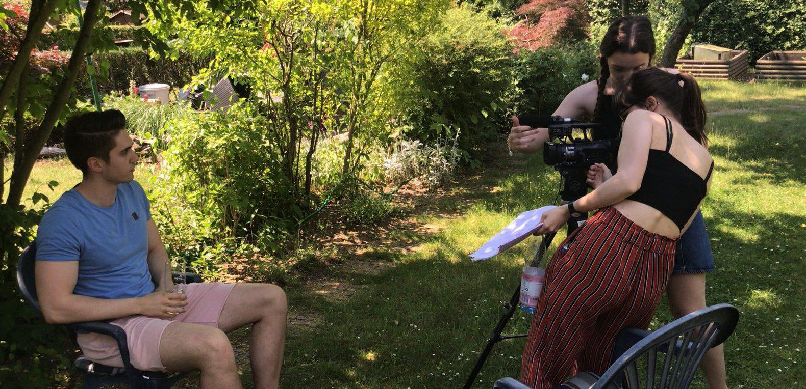Ein junger Mann sitzt auf einem Stuhl in einem Garten. Zwei junge Frauen filmen ihn.