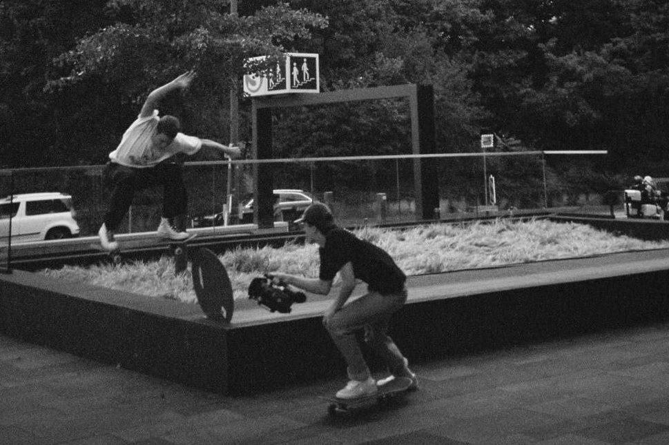 Zwei junge Männer auf Skateboards. Einer macht gerade einen Trick, ein anderer filmt ihn. Im Hintergrund Autos und eine S-Bahn-Station.
