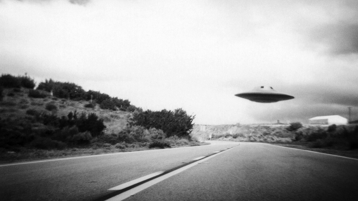 Flying saucer above highway