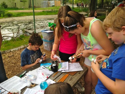 Helia Silveira, Ellie O'Donnell, Garrett Silveira and Owen O'Donnell working on a piping plover chick craft. Credit: USFWS