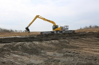 The Komatsu Excavator moves sediment into position and levels the ground by dragging the bucket back and forth across the marsh.