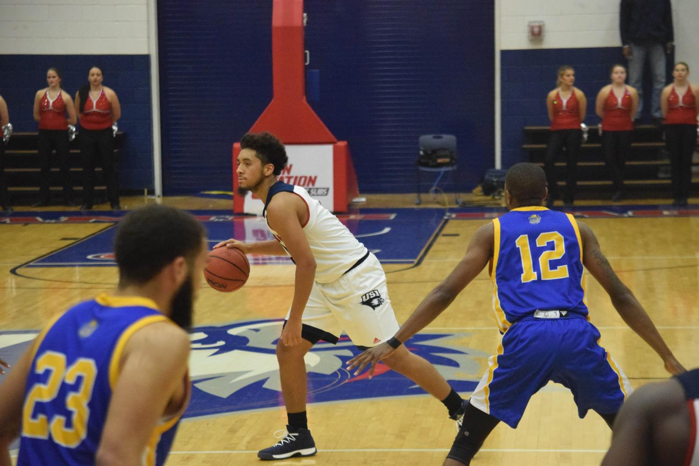 Mateo+Rivera%2C+freshman+guard%2C+moves+the+ball+against+Fisk+University.