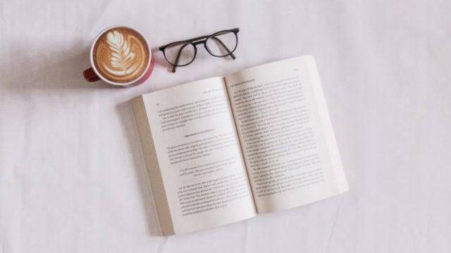 開かれた本とメガネとラテ