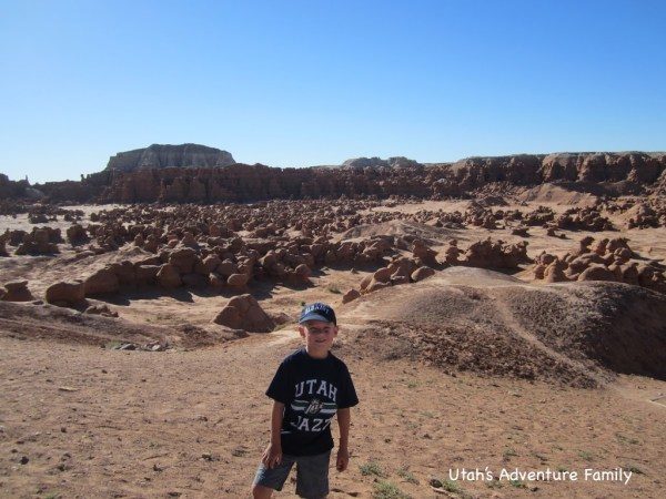 Our 7 year-old in front of the Goblin Valley floor where you can blaze your own trail.