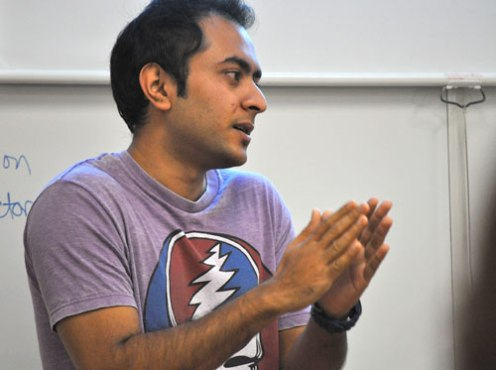 Senior history major Arif Abrar, a pre-Law student, talks with Arlington ISD students during an April 2 workshop on the UT Arlington campus. Abrar will attend law school in the fall. (Photo by James Dunning)
