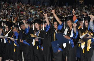 Graduating students sing the UT Arlington school song Friday, May 15, at the College of Liberal Arts' Spring 2015 Commencement at College Park Center. (Photo by James Dunning/COLA Communications)
