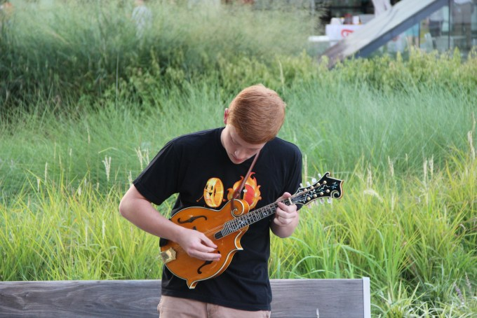 A young volunteer plucks at a mandolin in front of the Winspear Opera House downtown.