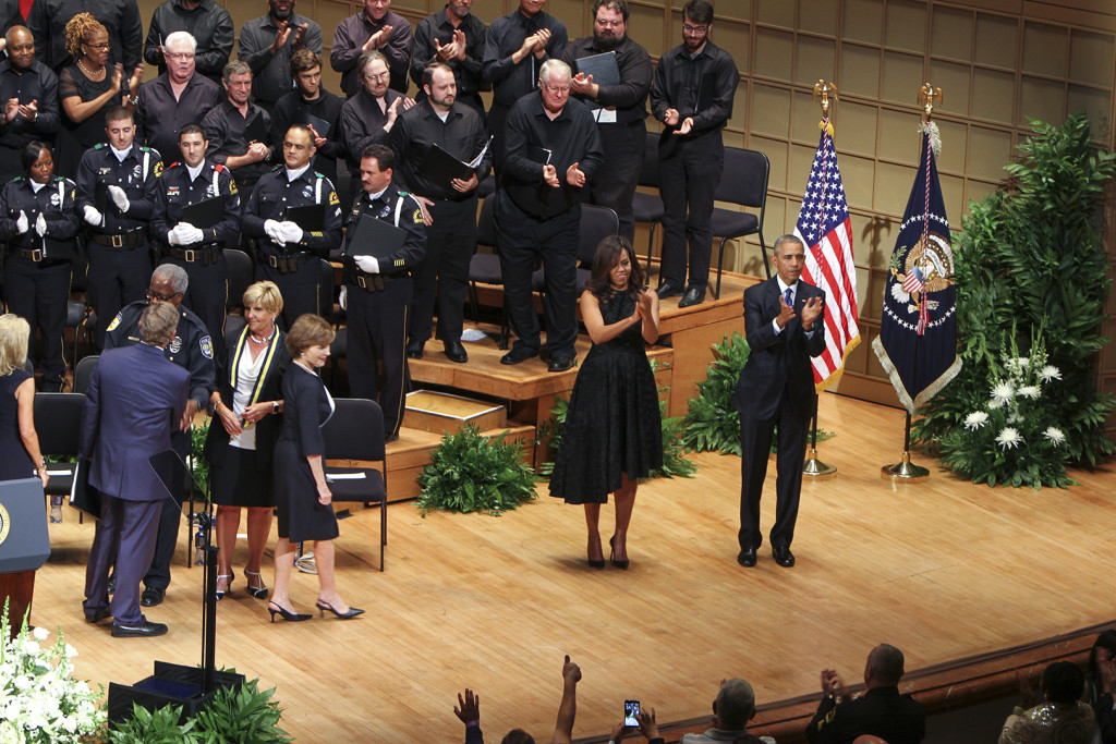 "President Obama and First Lady Michelle Obama attend the memorial service to honor the fallen officers as well as to urge the American people to ""open their hearts and stop the hateful rhetoric"" that has plagued the nation."
