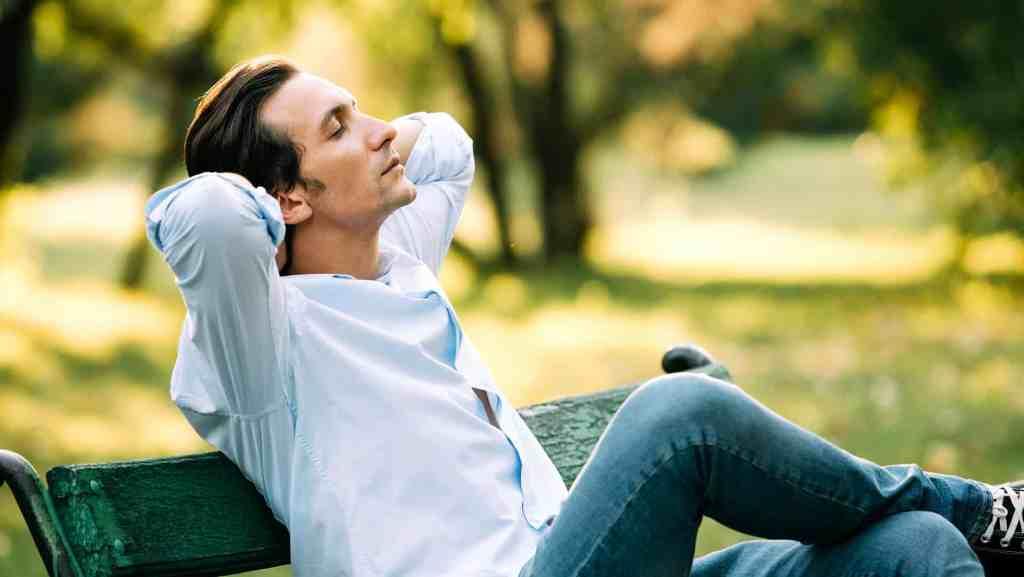 Ung man sitter tillbakalutad på en parkbänk.