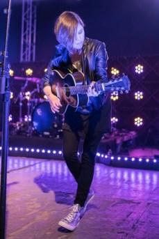 Tegan Quin of Tegan and Sara jamming on acoustic guitar.