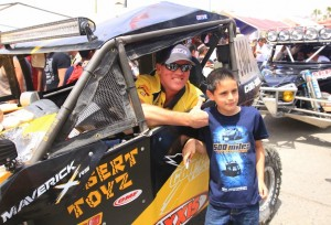 Cory Sappington and his No. 1904 Desert Toyz/ Can-Am Maverick 1000R X rs pose with a young fan at the starting line of the 40th annual Baja 500 in Mexico.