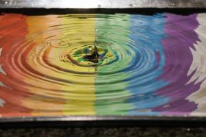 time lapse photography of water ripple with rainbow reflection