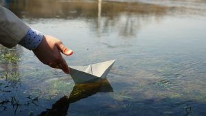 hand placing paper boat in the water