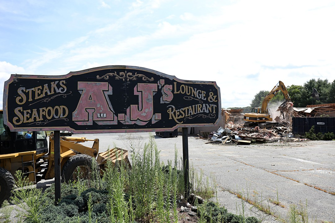 """A sign for AJ's Steakhouse stands behind a demolition site on Wednesday, Aug. 16, 2017, near Sykes Mountain Avenue in White River Junction, Vt. The lot, and the closed bowling alley behind it, will become a new Subaru Dealership. The previous owner, Doug Johnson, of White River Junction, was there to witness part of the demolition and said he bought the property in July of 1985. """"It was very nice to make a sale,"""" Johnson said. """"But there's a lifetime of memories here. It makes it a little bittersweet."""""""