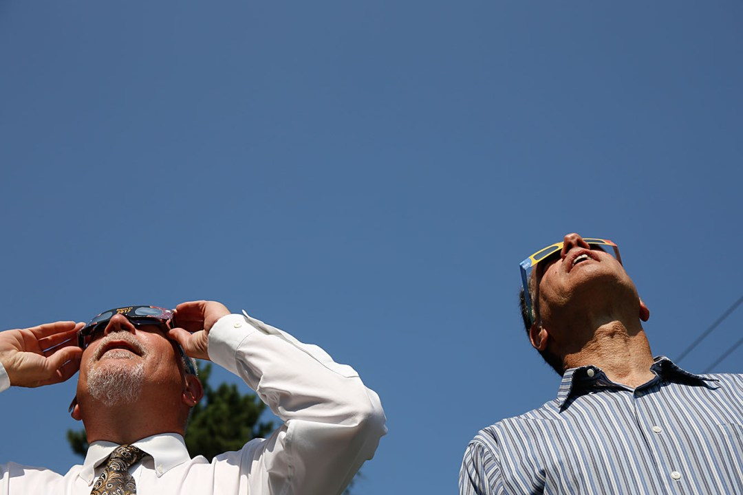 Valley News Publisher Dan McClory, left, and Editor Martin Frank take a look at the solar eclipse on Monday, August 21, 2017, at the Valley News office in West Lebanon, N.H.