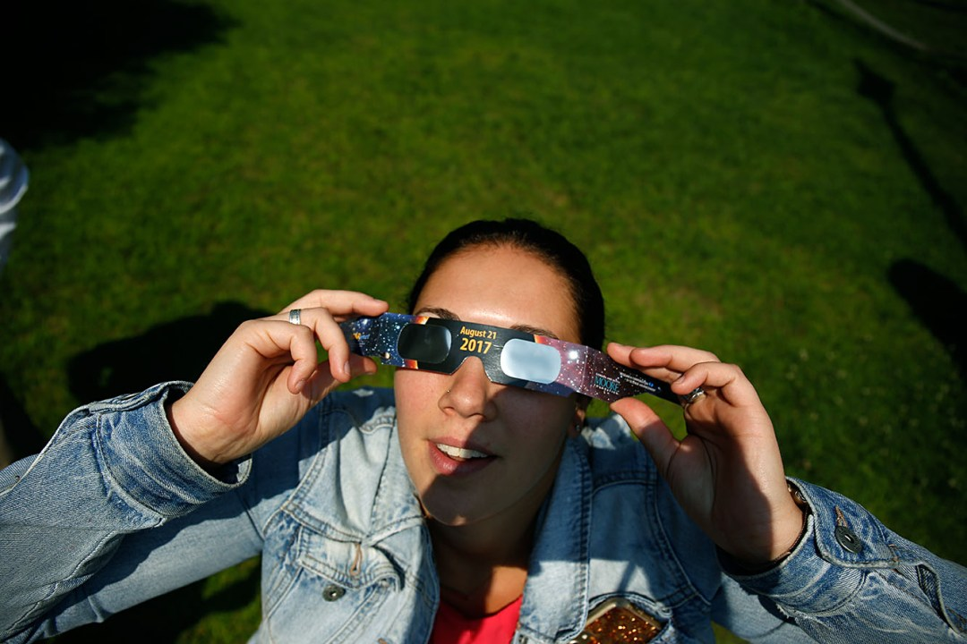 Valley News cops and courts reporter Jordan Cuddemi views the solar eclipse on Monday, August 21, 2017, at the Valley News office in West Lebanon, N.H.