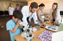 Miles Grunvald '18 gets kids acquainted with microscopes during a family friendly science session at Reunion 2015.