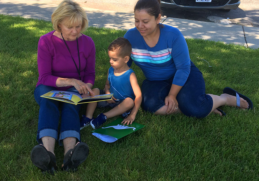 Kids reading in lawn to work on summer learning