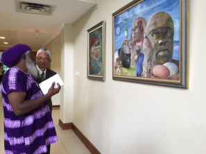 Lecturer and artist Clinton Hutton views his work with out-going UWI VC Nigel Harris