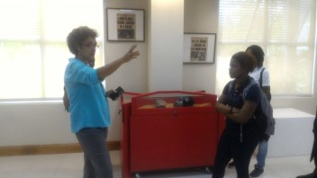 UWI Museum Curator Suzanne Francis-Brown talks with UWI Mona Accounting students visiting the exhibition