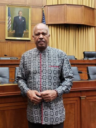 Professor Sir Hilary Beckles under a portrait of former Congressman John Conyers at US Capitol.