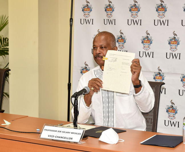Professor Sir Hilary Beckles displays his signed copy of the MOU between The University of the West Indies and the University of St Martin.