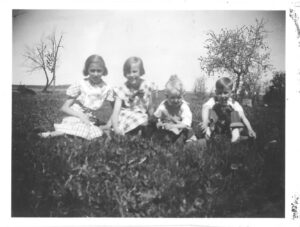 Black and white photo of a farm with trees in the background showing four children: Neva sitting on the left with short curled hair and a gingham dress, nest to her Beuna sits with short parted hair and a checkered dress with a bow on the neckline, Burr is seated wearing a shirt and trousers, and Add is seated on the right wearing overalls.