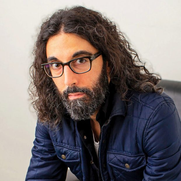 Photo by Barry Phipps. Picture of Daniel Khalastchi with long curly hair and beard, wearing dark-rimmed glasses and navy jacket, sitting in a Herman Miller chair and looking seriously at the camera.