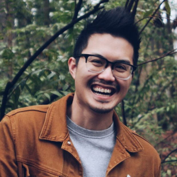 Photo by Elisa J. Fuhrken of Joshua Nguyen with dark spiked up hair wearing two-tone black and clear framed glasses, wearing a gray shirt with a tan corduroy jacket, standing in a green woodsy area, looking into the camera and laughing.