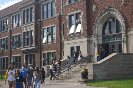 """Freshman students tour the campus during the """"Day of Welcome."""" A group of students exit Old Main."""