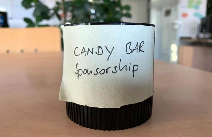 Paper clips container with a post-it. Reads Candy Bar Sponsorship.