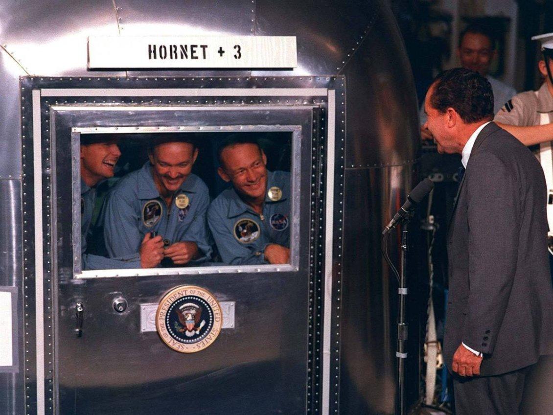 Başkan Richard Nixon, Apollo 11 ekibi Pacific'e iniş yaptıktan sonra onları ziyaret etti. Ekip, suya inişleri sonrası karantina tankına alınmıştı. Fotoğrafta, ekibin Richard Nixon'ı karantina tankından selamlaması görülüyor.