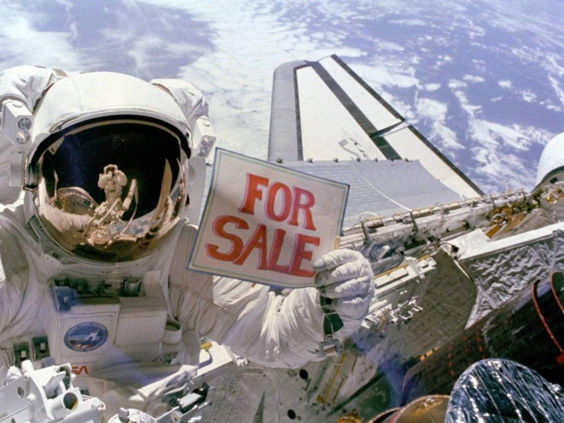 """Astronot Dale A. Gardner, 1984 yılındaki uzay aracı dışı görevinde, iki bozuk uydunun yanında, elinde bir """"satılık"""" levhası tutuyor."""