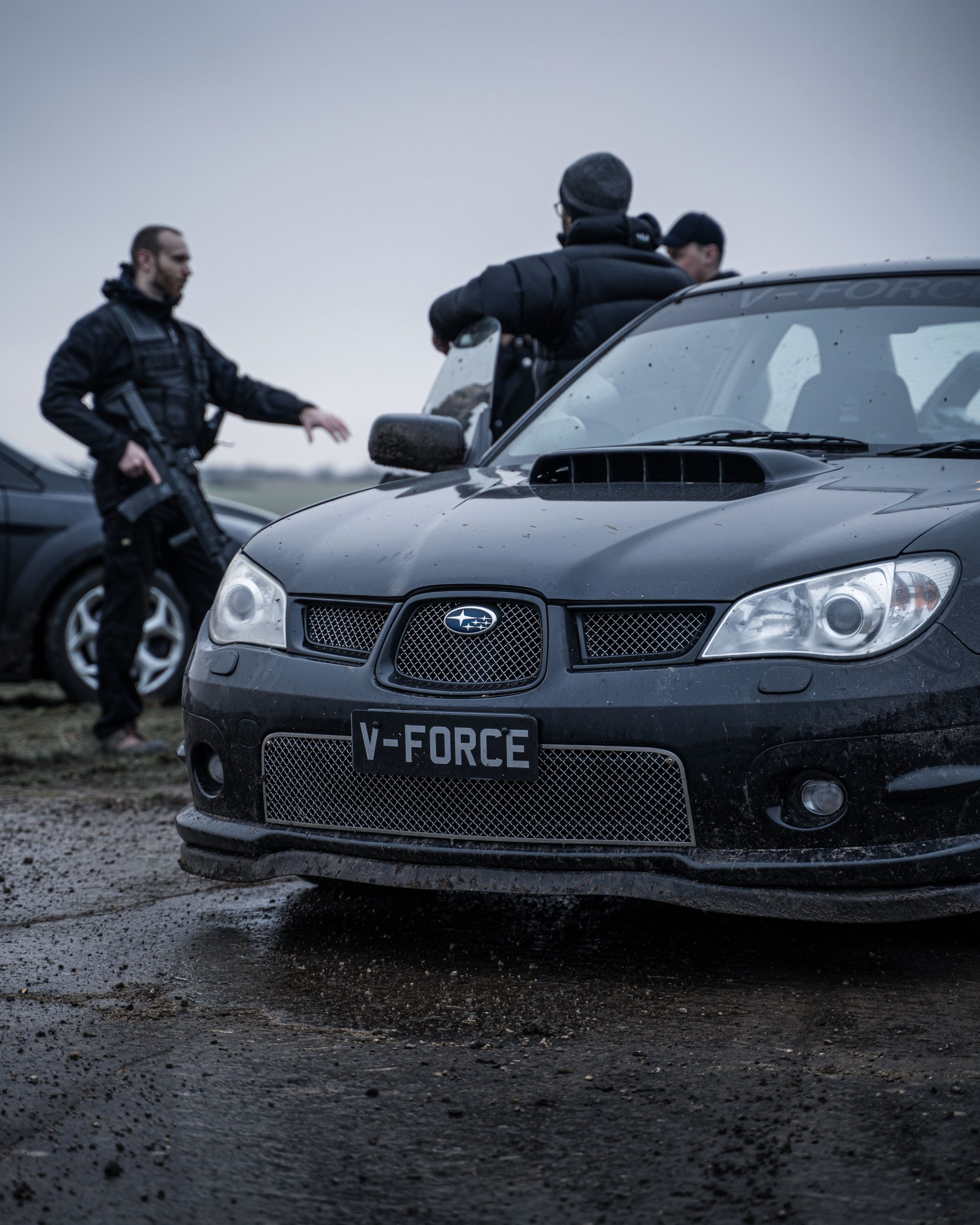 Men dressed in black standing next to a Subaru Rally Car with a C8 assault rifle as part of Vehicle Gunnery