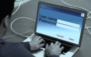 man typing in username and password on laptop