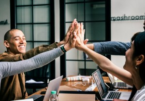 people in office doing group high five - Top 4 Advantages to Using an IT Managed Services Provider, Plus the Key Tech Solutions Your Business Needs to Succeed