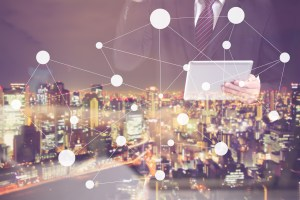 business man on tablet overlooking city - Small Business IT Security Basics, Part 1: 5 Essential Steps for Ensuring Cybersecurity