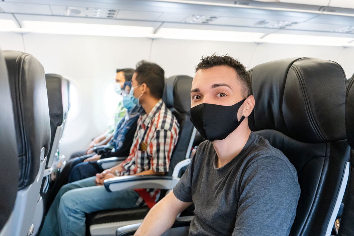men with masks on airplane