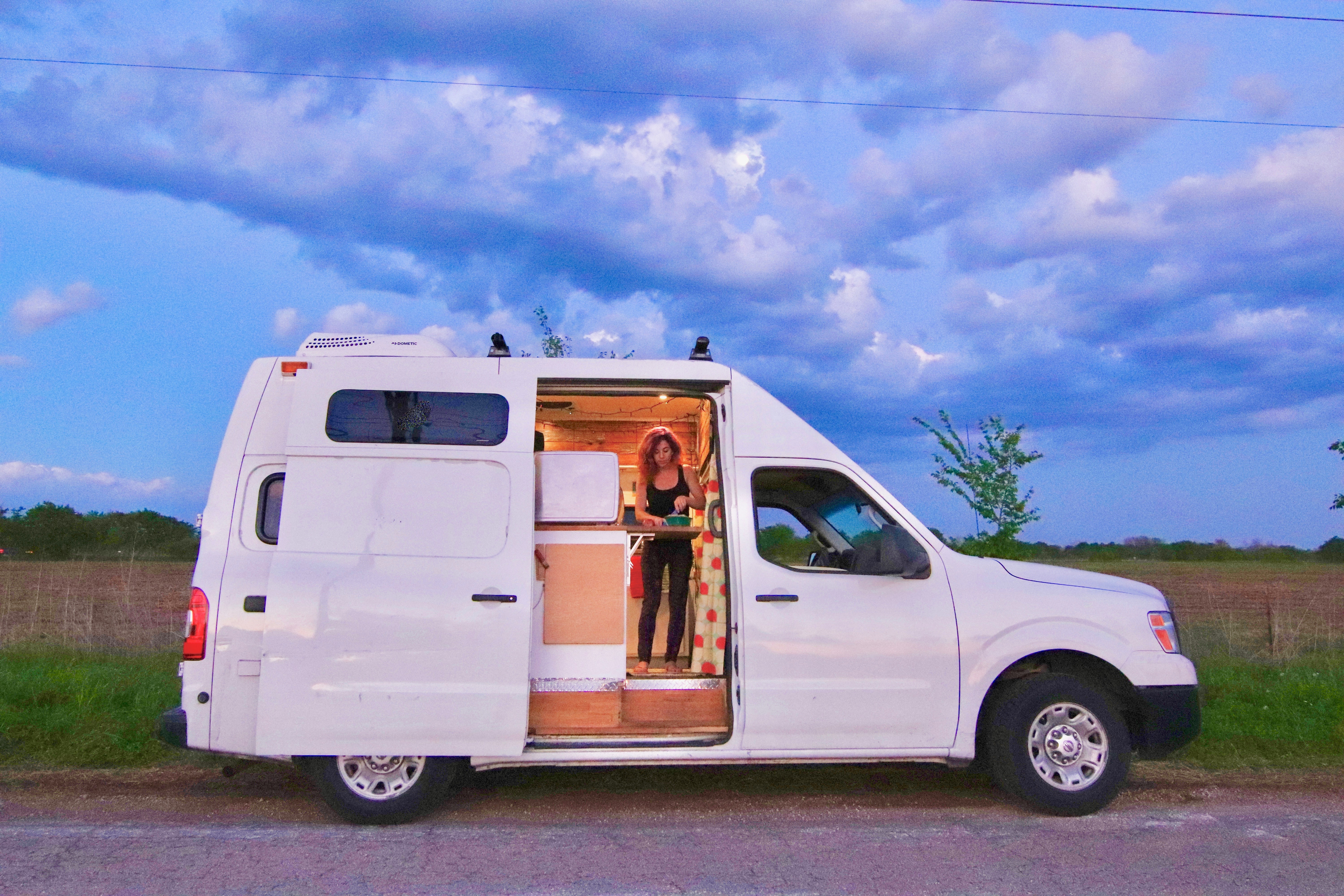 girl cooking dinner in diy camper van nissan nv2500 vacay vans