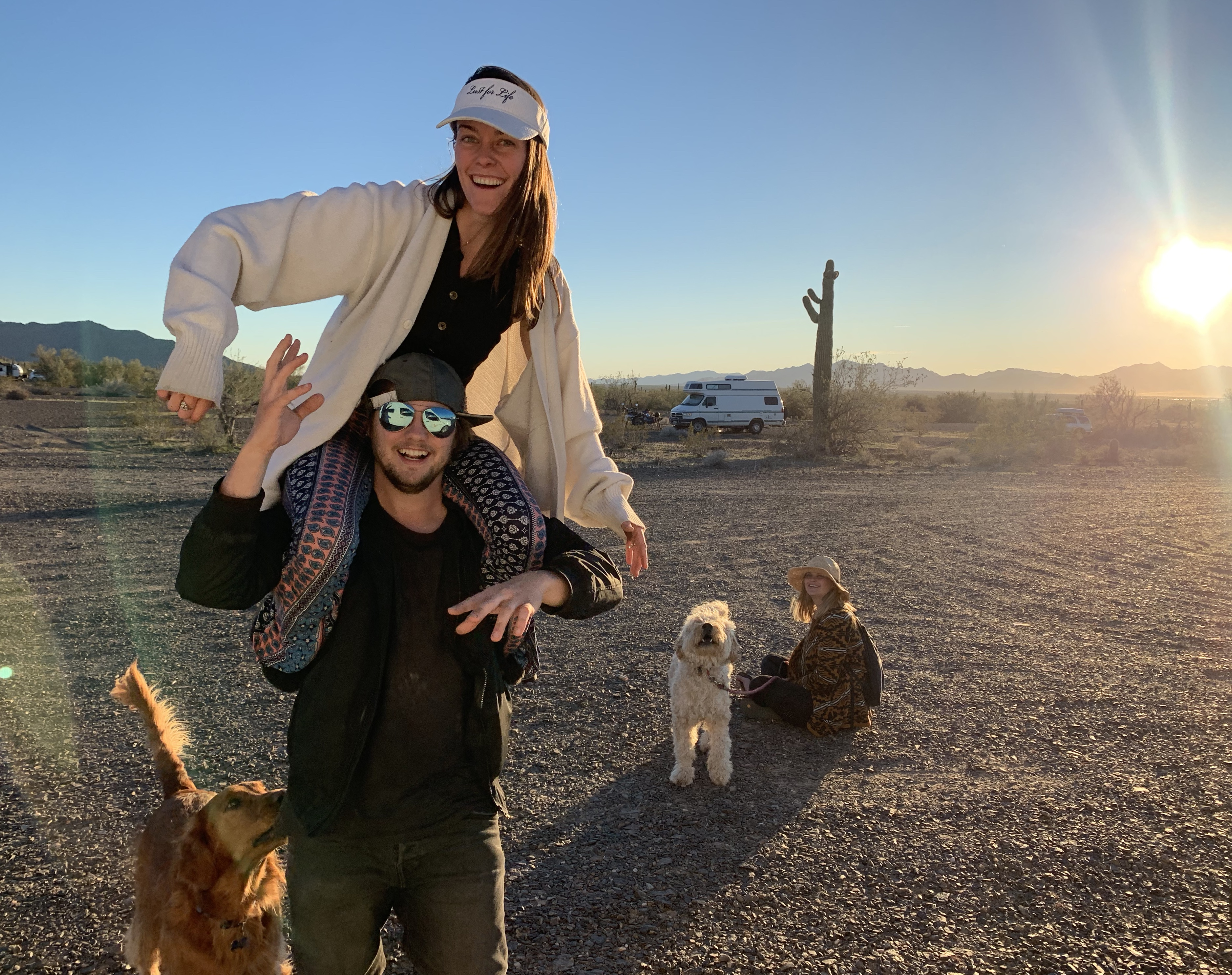 vanlife gathering friends with dogs desert sunset