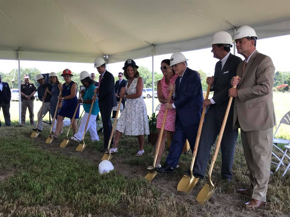 Officials in hardhats with shovels for groundbreaking ceremony