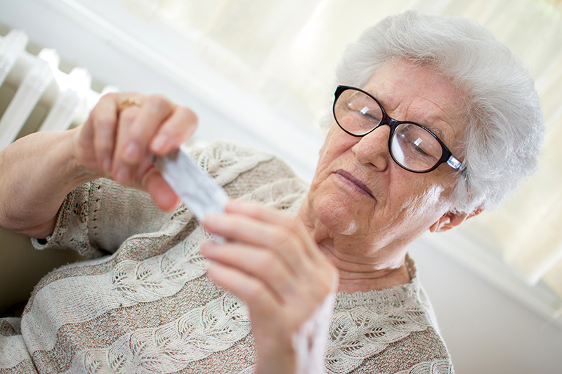 Close-up portrait of senior woman with glasses reading pill package