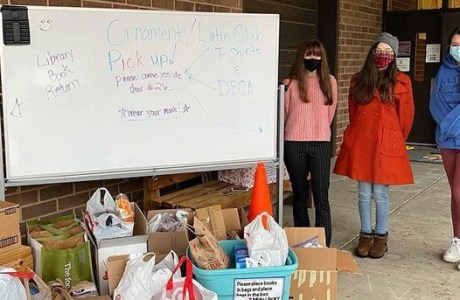 High Schoolers standing by their donations
