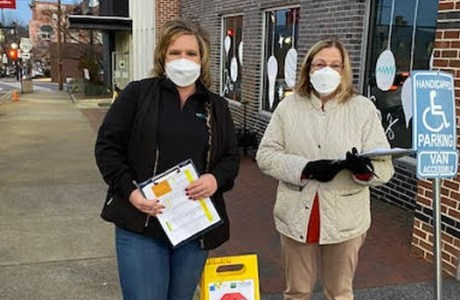 Two PATHS staff members outside of a vaccine clinic
