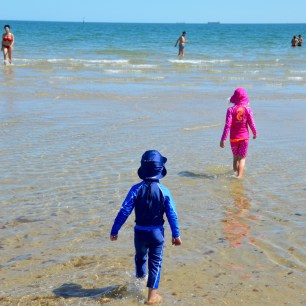 Barnen svalkar sig på stranden i St. Kilda