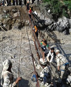 In this handout photograph released by the Indo-Tibetan Border Police (ITBP) on June 21, 2013, ITBP personnel aid flood evacuees across a raging river in Ghangaria following heavy rain in the region. Rescue workers recovered scores of bodies from the Ganges river in northern India on June 21, as the death toll from flash floods and landslides topped 200, with thousands of mainly pilgrims and tourists still stranded. Ghangaria is base for world famour valley of flowers and Hemkund gurudwara